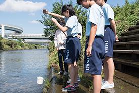 こぼれないよう慎重に川の水を汲む生徒たち